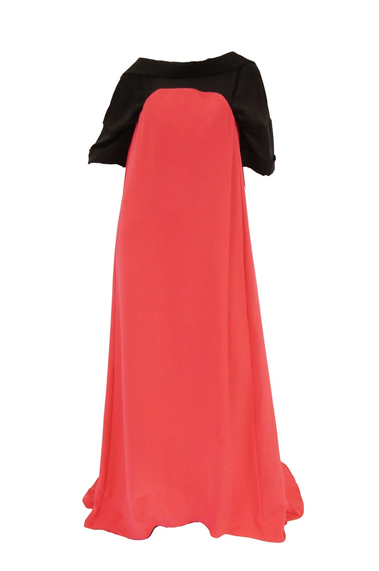 Absolutely incredible magenta pink and black evening dress by Oscar de la Renta. The dramatic dress is composed of two connected parts. The black base dress with a wide bateau neckline and loose sleeves that fall just above the elbow, as well as a