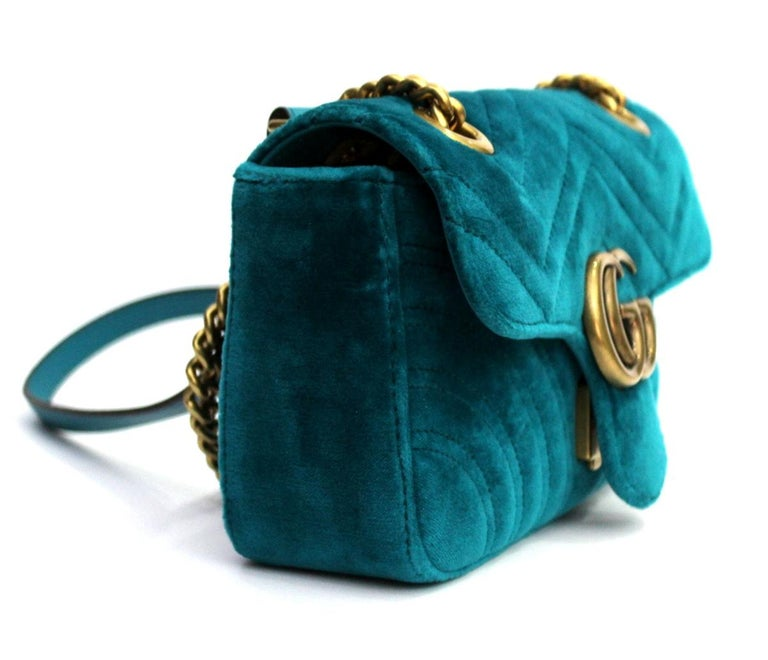 -Petrol blue velvet with chevron pattern and heart; -Antique gold-colored finishes; -Double G; -Inside pocket with zipper; -The sliding chain shoulder strap can be worn as a shoulder strap, height (light) 55cm, or with double handles, height (light)