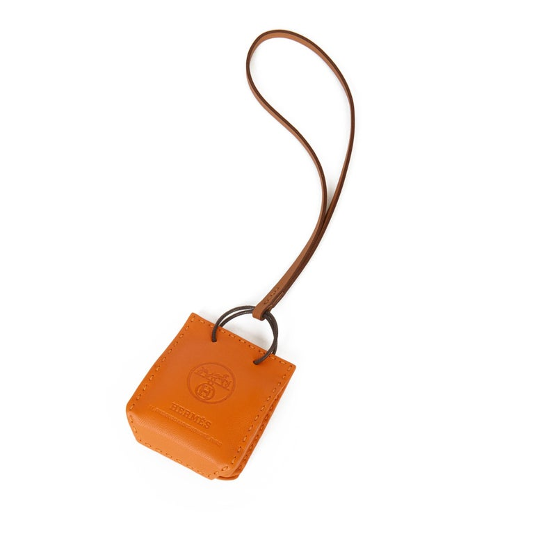 HERMÈS Orange Lambskin Leather Shopping Bag Charm  Xupes Reference: SKHB014  Age (Circa): 2020 Accompanied By: Hermès Box Authenticity Details: Date Stamp (Made in France)   Colour: Orange Material(s): Lambskin Leather   Height: 5cm Width: