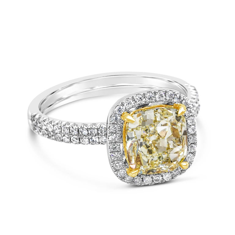 Showcasing a 2.03 carat cushion cut yellow diamond center, set in a floating halo of round brilliant diamonds. Double-row diamond mounting made in 18 karat white gold. Accent diamonds weigh 0.37 carats total.  Style available in different price