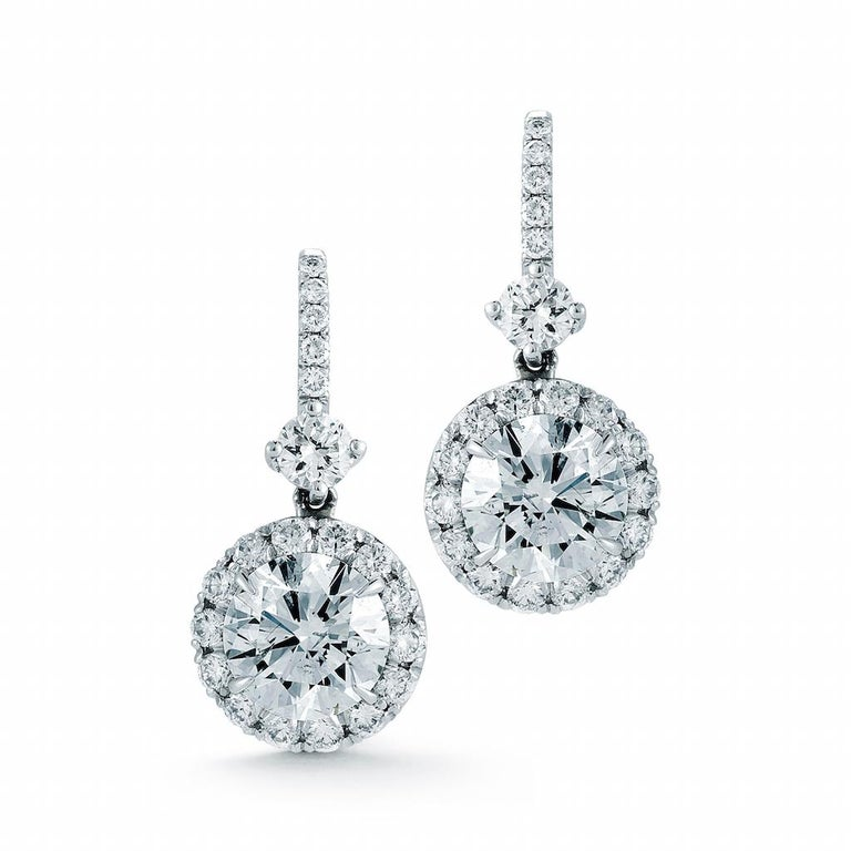 2.03 Carat total weight Dangling Halo Diamond Earrings in 18K White gold Pair of dangling earrings with 2 matched round brilliant center diamonds weighing .70 carats each  complemented by a diamond halo consisting of 40 round brilliant cut diamonds