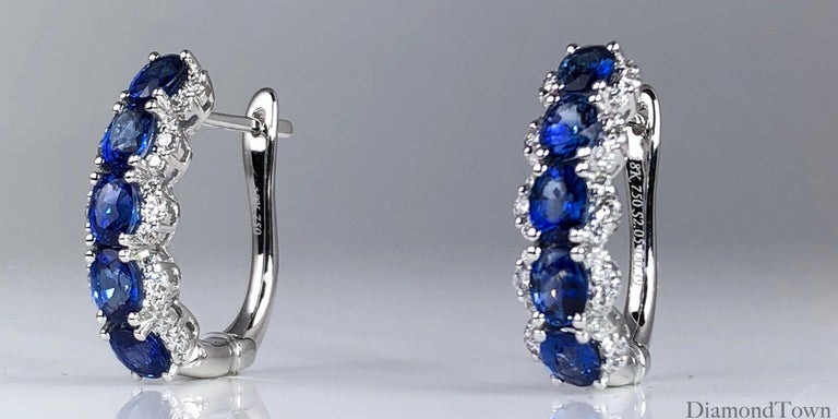 These lovely hoop earrings feature 5 oval cut blue sapphires (total weight 2.05 carats), wrapped among round diamonds (total diamond weight 0.39 carats). The earrings close securely by lever-back. Set in 18k White Gold.  Many of our items have