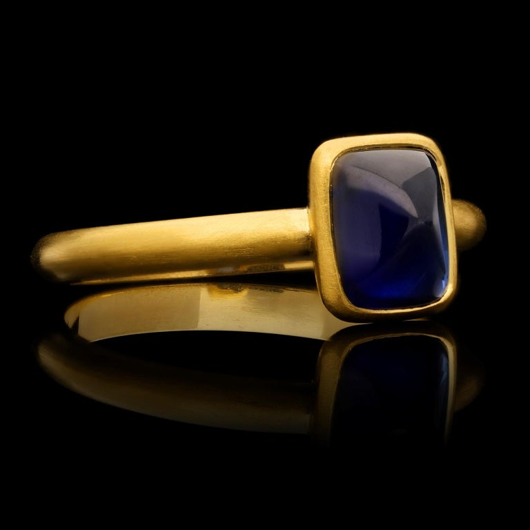A contemporary Burmese sapphire and gold ring by Hancocks, set with a cushion shaped sugar loaf unheated Burma sapphire of rich blue colour weighing 2.06ct, rubover set in a finely crafted handmade 22ct yellow gold mount with beautiful satin finish