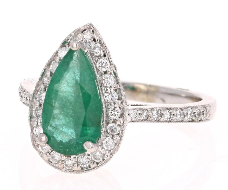 Beautiful Emerald Diamond ring with an eye catching Halo! A unique way to propose and add color to your accessory collection.  The Pear cut Emerald is 1.46 Carats and is surrounded by 75 Round Cut Diamonds at 0.61 Carats. The Clarity and Color of
