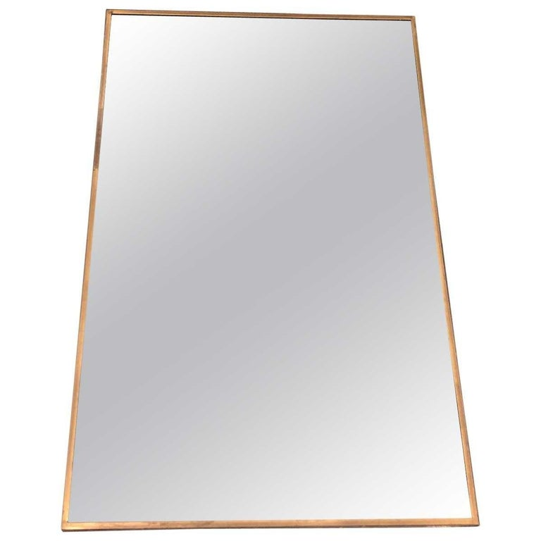 Mirror. Antiqued brass X-form base.  Materials: Antiqued brass, mirrored glass Dimensions Width 19