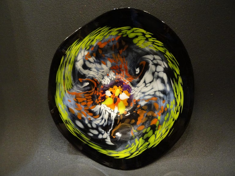 Unique and very refined piece of glass, blown glass, 20th century. A large black dish, with a psicoledic design in different colors, orange, green, yellow, blue and white. It's a craft made piece. On the back it makes another amazing design in black