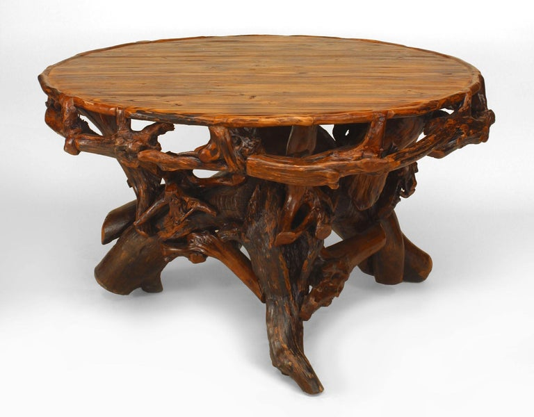 Mid-late 20th century American Rustic Adirondack style round dining table with a root pedestal base supported on three legs with a filigree apron.