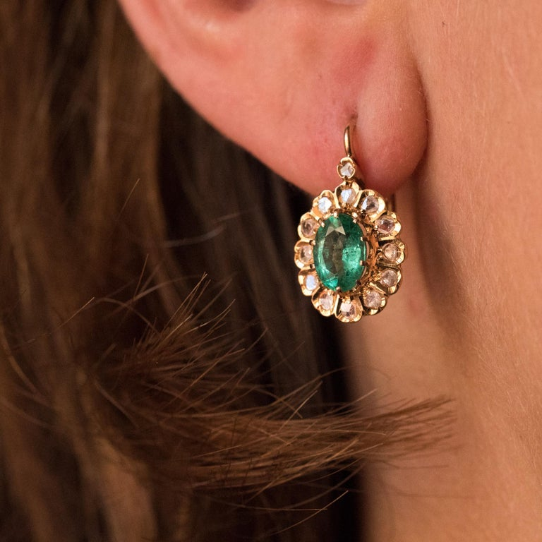 For pierced ears. Earrings in 18 karats rose gold. Lovely antique earrings, they are set with claws on their top of an oval emerald, surrounded by rose-cut diamonds, like a daisy. A rose-cut diamond overcomes the whole. The clasp system is from the