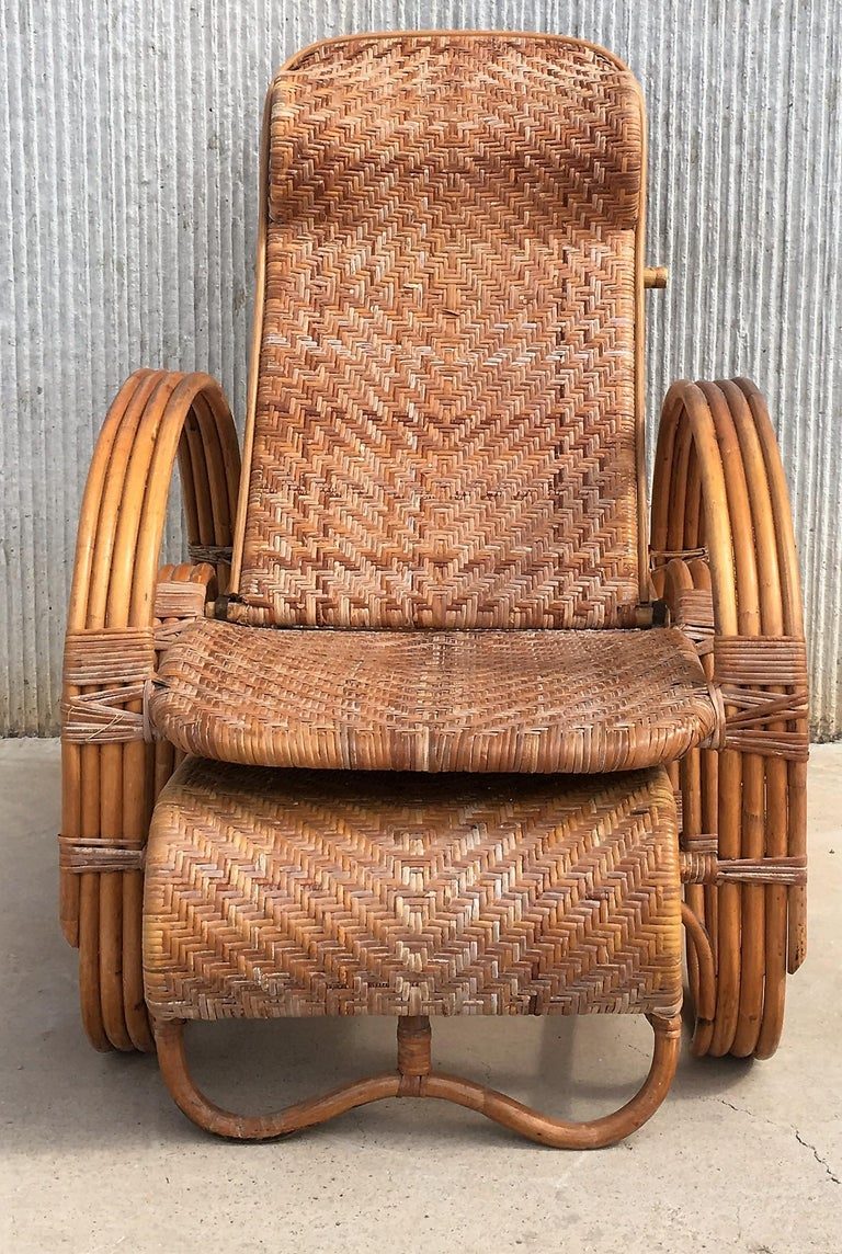 A height-adjustable chaise longue made of a bentwood frame with woven rattan.