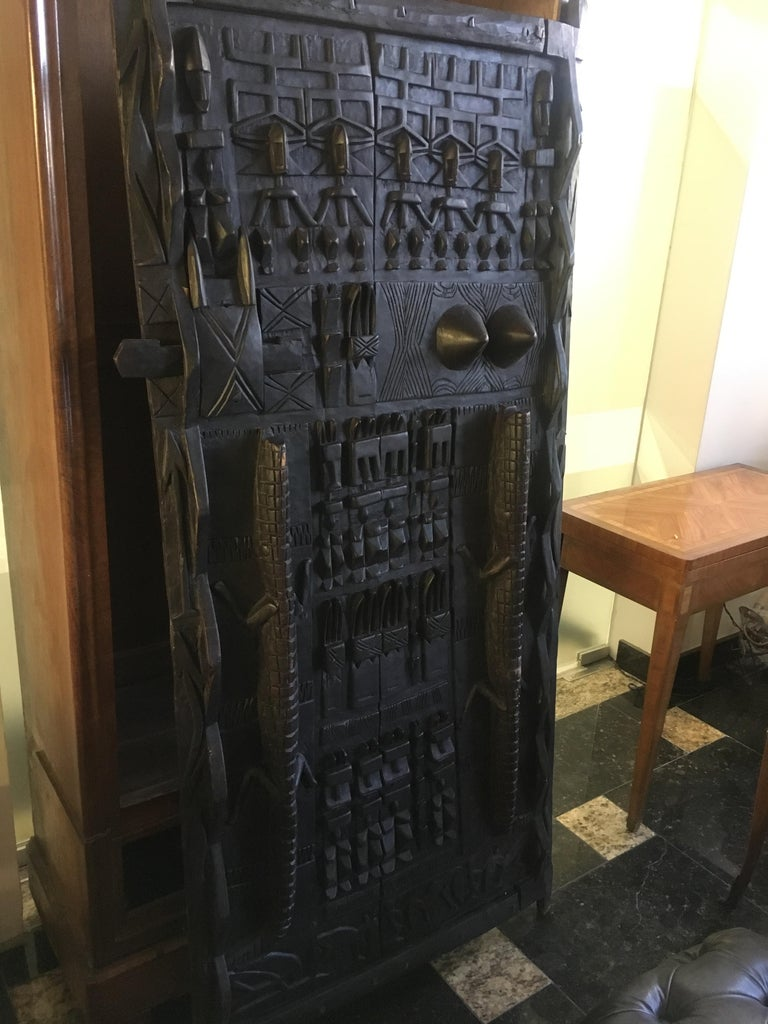Carved wood door decorated with crocodiles, characters and geometric symbols. (This model of door is not symmetrical and presents differences of size from one angle to another) Africa, circa 1900 Measures: 181 x 83 cm.