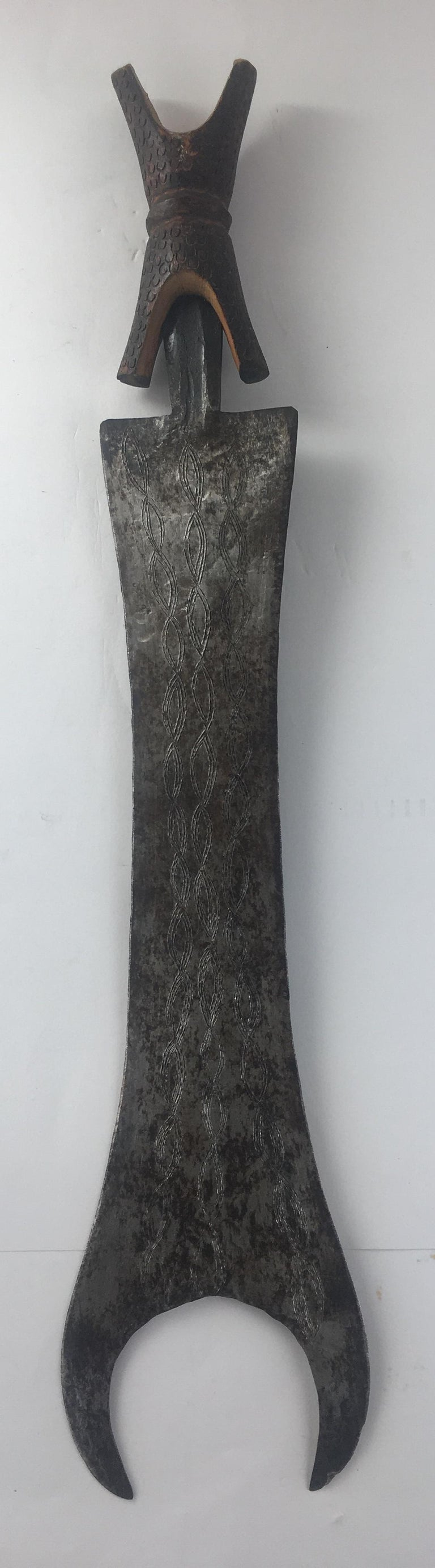 African ceremonial sword from the democratic Republic of Congo, circa 1920s. Iron and wood, in a case made of cloth and animal skin.  This status symbol tribal sword is carried is a single edged, iron blade engraved with elaborate patterns on both