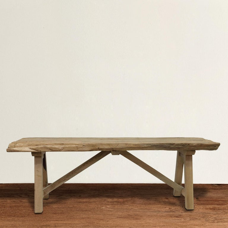 A strapping 20th century American trestle table with A frame legs supporting a live edge oak slab, all with a weathered bleached finish. Perfect as a console table behind a sofa, in your entry, or under a TV in your family room.