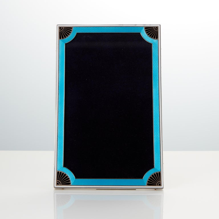 A superb quality cast silver frame with applied two color enamel? The underlying color is aqua marine with applied black enamel decoration to leading edges & four corners? There appears to be no damage to the silver & enamel? The leather back &