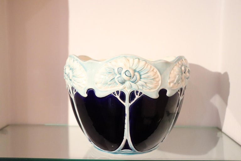 Beautiful Art Nouveau blue ceramic vase, 1920s. The body presents a refined work with decorations in relief flowering trees that surround the vase and are typical of the Art Nouveau era. The vase is colored in enamel blue tone and blue decorations.