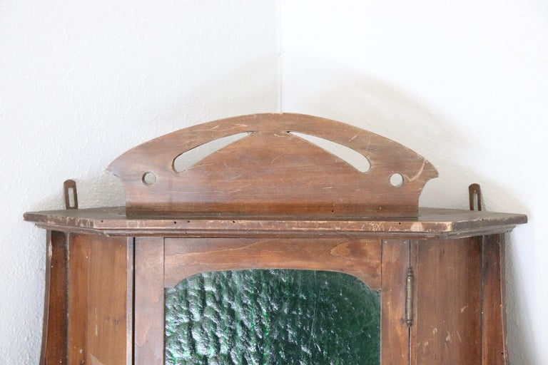 Italian small Art Nouveau corner cupboard about 1905. High quality furniture in solid Poplar. This corner unit needs to be fixed to the wall. Particular front door with antique green glass. On the sides, decoration with volutes of typical Art