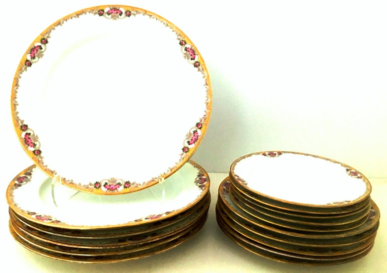 Mid-20th century Art Nouveau Limoges France hand painted porcelain and 22-karat gold. Set of seventeen pieces dinnerware set by. M. Redon. This timeless, Classic and coveted pattern features a bright white ground with yellow, pink and green floral