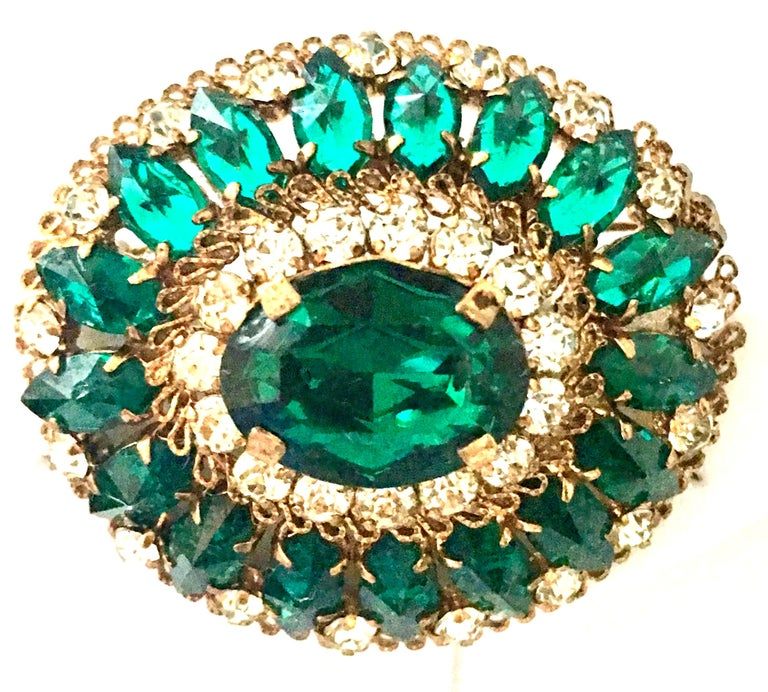 20th Century Gold Plate And Austrian Crystal Oval Dome Brooch-Signed. This fantastic piece is executed with gold plate prong set brilliant cut and faceted emerald green and crystal clear Austrian crystal stones. Features the finest quality in