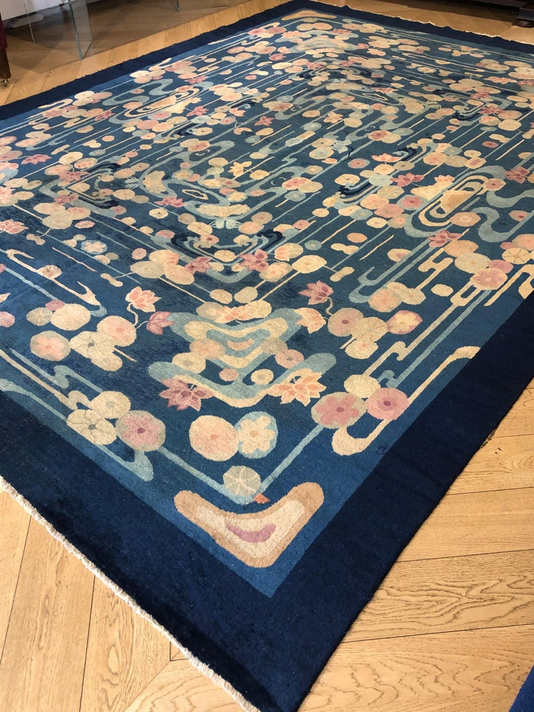 An important and rare example of a Chinese-made Art Deco Liberty carpet. The decoration reproduces a pond full of water lilies and other aquatic flowers in a harmonious composition that develops symmetrically. The flowers, like all the other