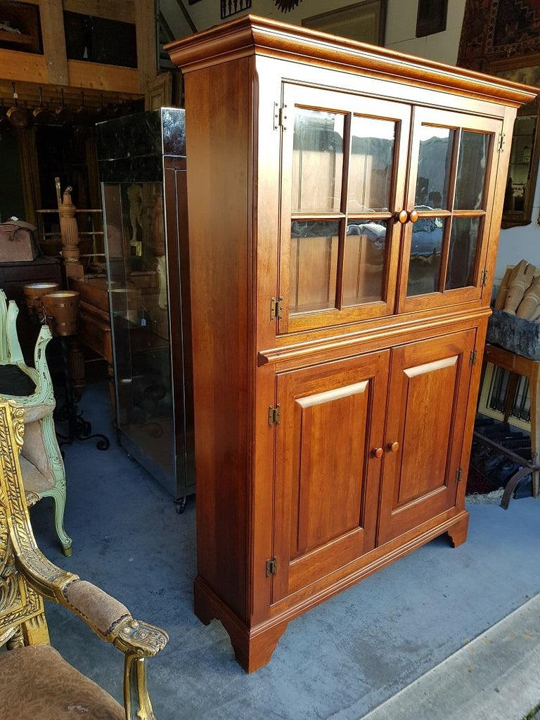 American cherry wood kitchen cabinet made by Bob Timberlake Lexington numbered 833-864 Kitchen Cupboard Made in USA, in the upper part 2 doors with glass panes behind which 1 shelf with slotted plates and at the bottom 2 doors behind which space for