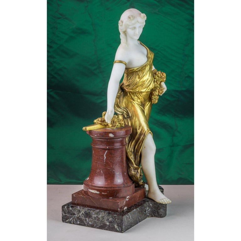 Exquisite bronze and marble figure of a woman with flowers by H. Fugère. In gilt bronze dress leaning on a marble column with flowers in her hand, on a shaped marble base. Artist: Henri Fugère (1872-1944) Date: circa 1900 Origin: French Size: 21 in