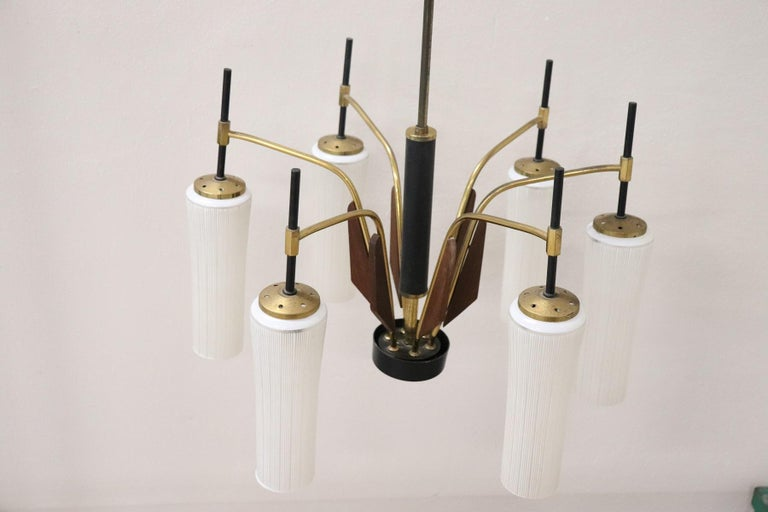 Beautiful and rare chandelier by Stilnovo Italian designer six arm with 6 lights. Solid brass structure, six arms with decorations in fine mahogany wood. The bowls are made of glass with special decorative lines. Only needs brass polishing.