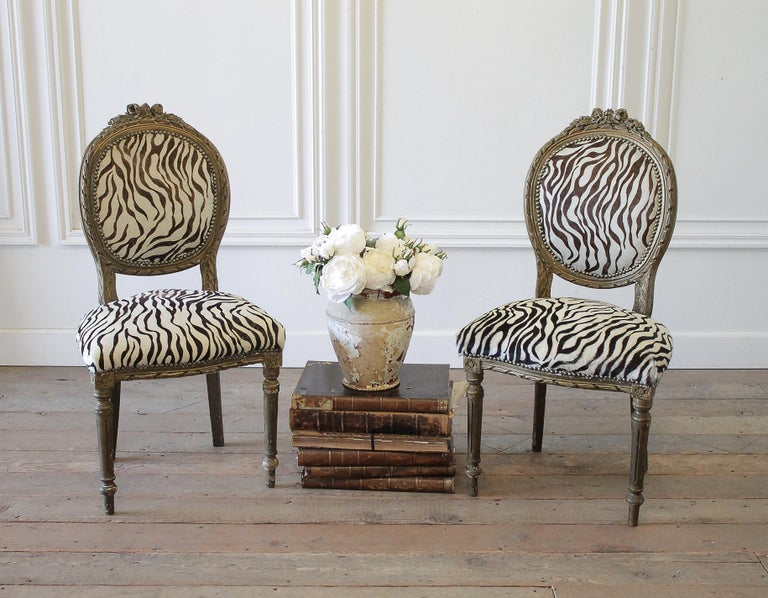 20th century carved giltwood zebra upholstered Louis XVI style chairs Gilt finish has an aged patina, with chipping exposing a white finish underneath. Legs are solid and sturdy. Upholstery is done in a zebra style printed hair on hide, with