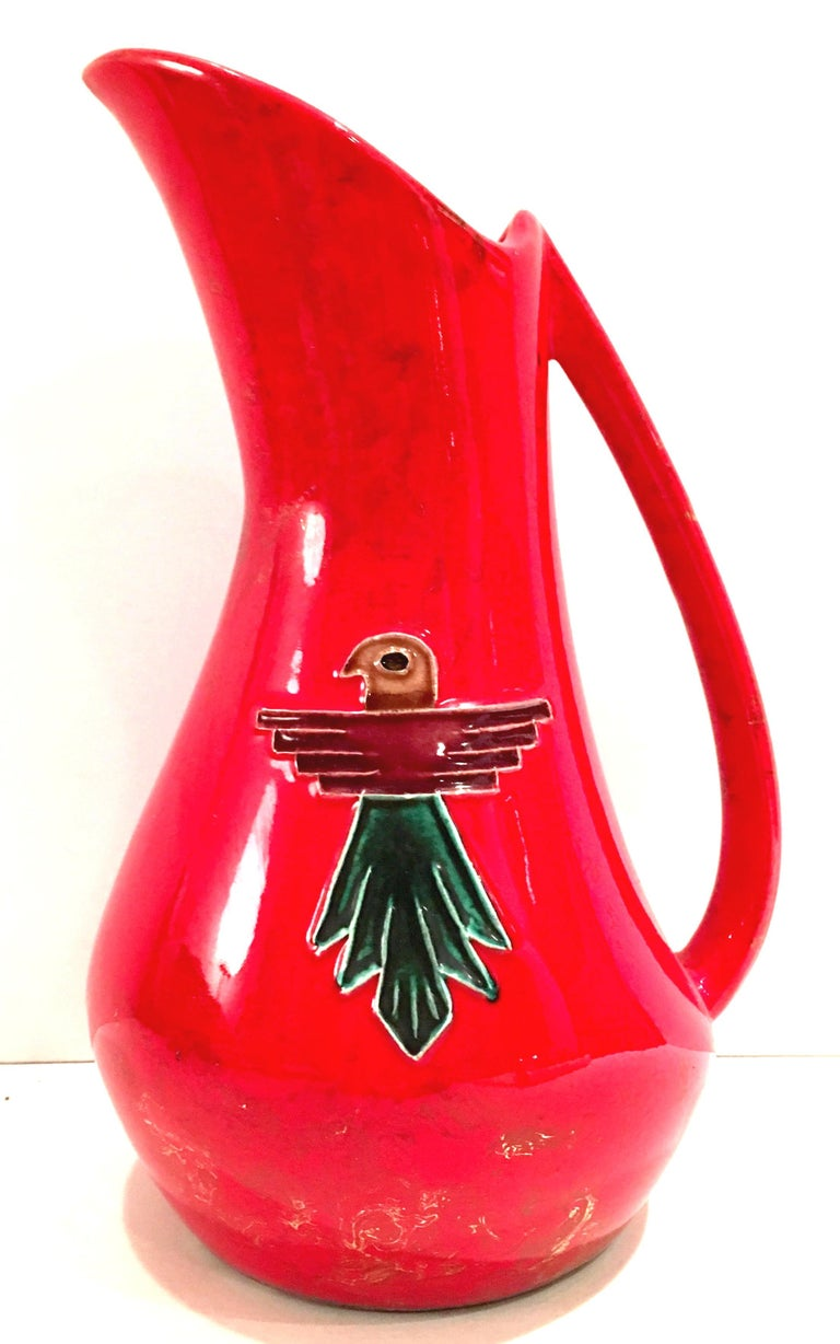 Mid-20th century ceramic glaze pottery, fire engine red with gold metallic detail and reposse Thunderbird hand painted detail five piece drinks set. Set includes handled pitcher and four tumblers. Tumblers measure, 4