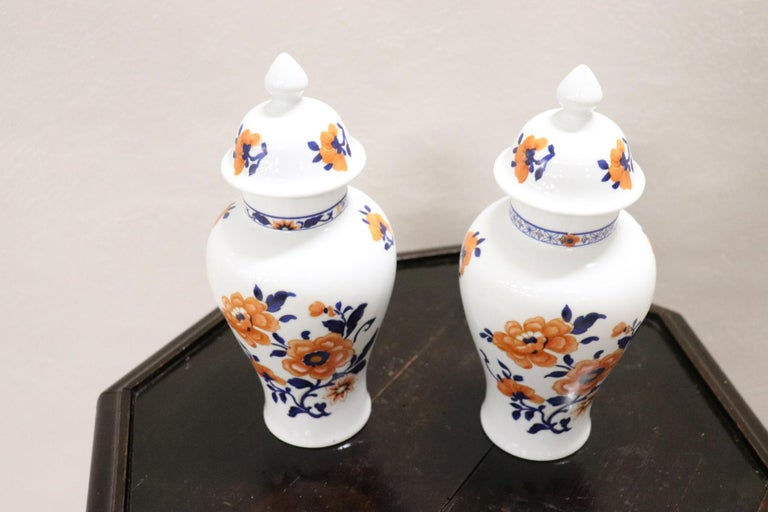Refined polychrome porcelain pair of vase, China, 1950s. Vases made of hand painted porcelain with orange floral motifs.