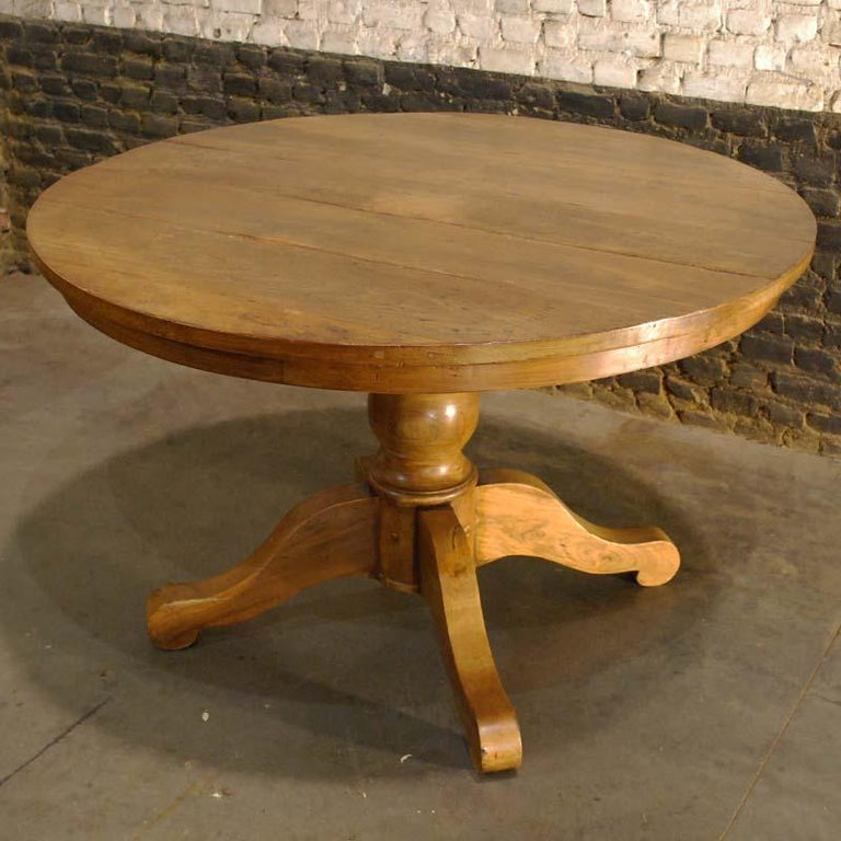 A beautiful country style round dining table on a baluster turned column with four splayed legs. The rustic table is made in solid teak and has a warm semi-gloss honey color. The table stands on four legs that guarantee stability more than three