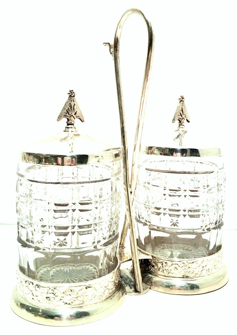 20th century cut crystal & silver plate cruet set of three pieces. This lovely cut to clear crystal and silver plate three-piece cruet set includes, two cut crystal cruet or condiment jars with silver plate lids and one silver plate caddy. Each jar