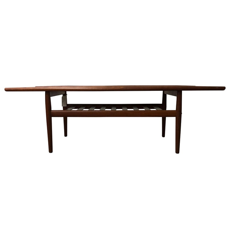 A vintage Mid-Century Modern Danish coffee table made of hand carved teakwood, designed by Hans J. Wegner and produced by Andreas Tuck, in good condition. Wear consistent with age and use, circa 1960 Denmark, Scandinavia.  Hans Jorgensen Wegner