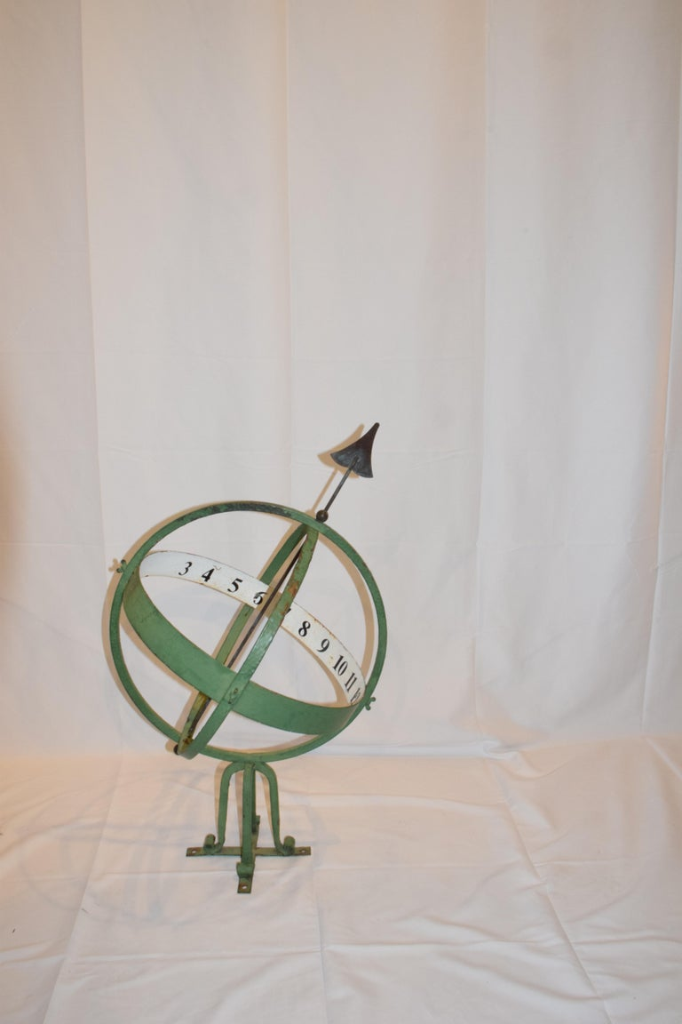 Found in England this 20th century armillary sphere is pierced with an arrow and mounted on a four foot scrolled base. The scroll base is mounted on a cross bar which can be attached to a surface, four holes are provided for additional stability.