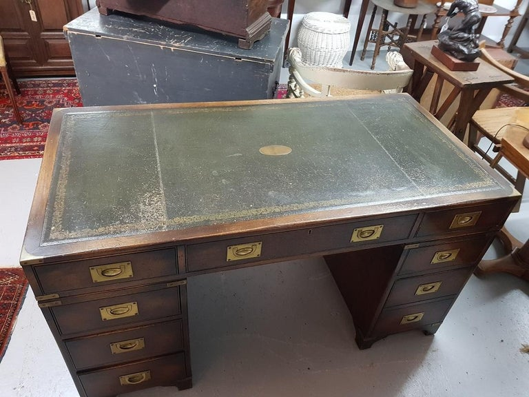 English mahogany colored military/Campaign desk with 8 drawers of which the middle drawer is a key further provided with brass fittings and on both sides of the drawer blocks a handle, this is made by Reprodux England, it is also in good condition
