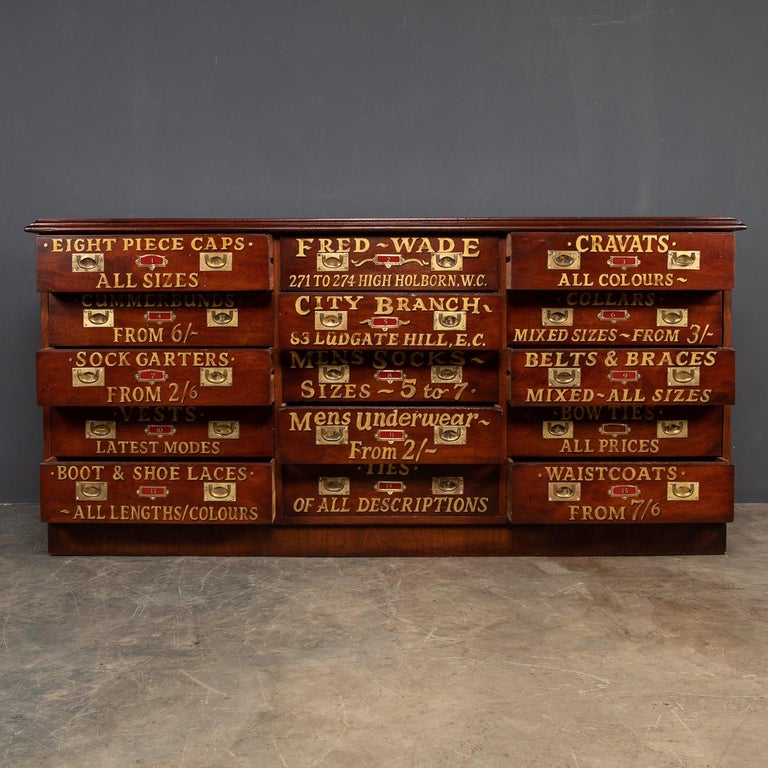 Antique early-20th century English hand crafted mahogany haberdashery, this unit would have been undoubtedly used in a prestigious gentleman's clothing store in the fashionable, 1900's. This piece has fifteen retractable drawers with original brass