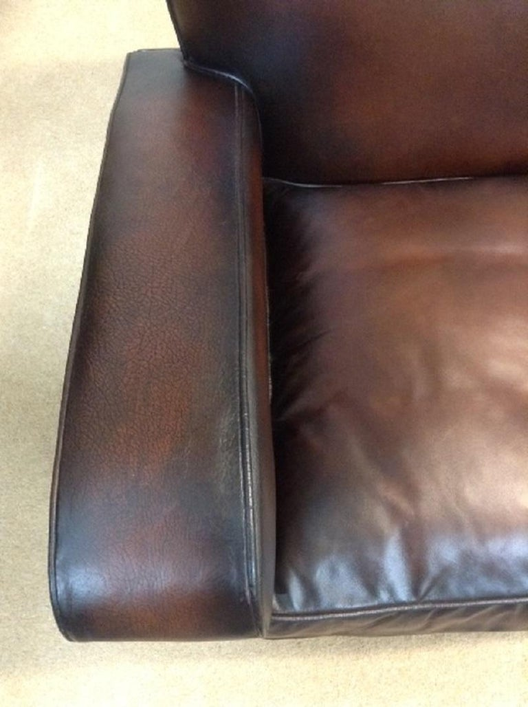 For sale is a good quality retro/vintage two-seat leather sofa which has been recently restored. The sofa has its original leather on both arms, front facings, seat border and piece along top of seat back, which show signs of age but are not