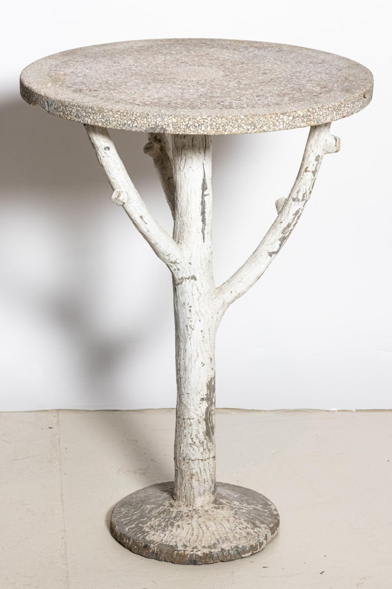Rustic cast stone garden table with white painted faux bois base, made in England circa early 1900s. Textured cast stone tabletop is supported by a sturdy base of rough-hewn branches. Tall with a petite round top, this occasional table is a nice