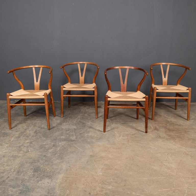 Iconic mid-20th century set of four Wishbone dining chairs, also known as the CH24 Chair or Y Chair is a chair designed by Hans Wegner in 1949 for Carl Hansen & Søn. The chair features a bentwood armrest and a paper cord rope seat in an woven