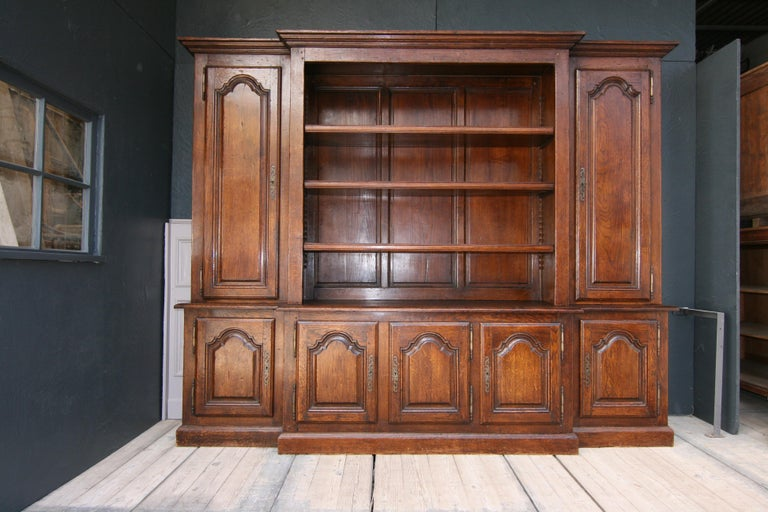 Large, high-quality French bookcase or cupboard from the 20th century, made of solid oak.  Lower part with 5 doors, behind which there are shelves.  Upper part with 2 large doors, each with 3 adjustable shelves, and a large open part in the