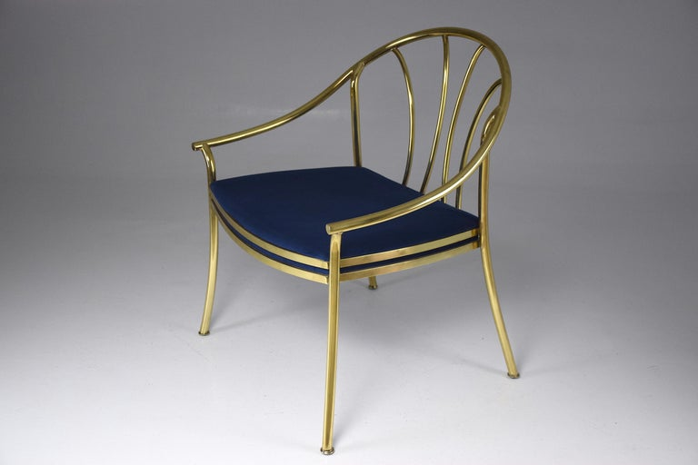 A beautifully crafted 20th-century French statement vintage armchair or side accent chair composed of polished solid gold brass and designed with a curve rounded backrest, panels and splayed legs. We have fully restored the chair through new