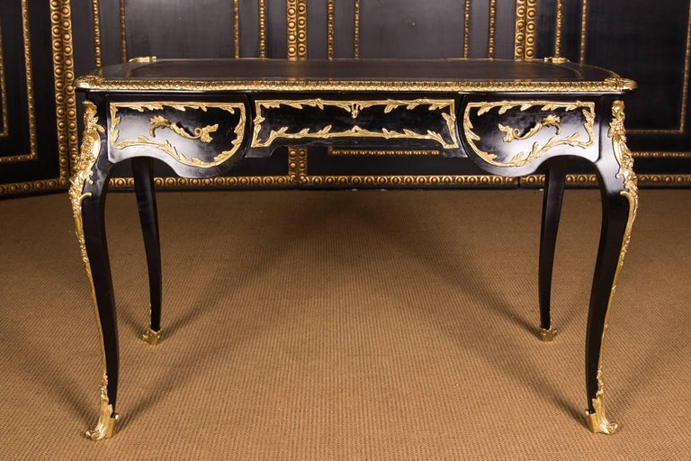 Black ebonized, four-sided passively curved frame base on high, elegantly curved squares. Encased in finely chiseled brass fittings. Slightly protruding tabletop with profiled decorated bronze lining and gold-imprinted leather imitation insert.