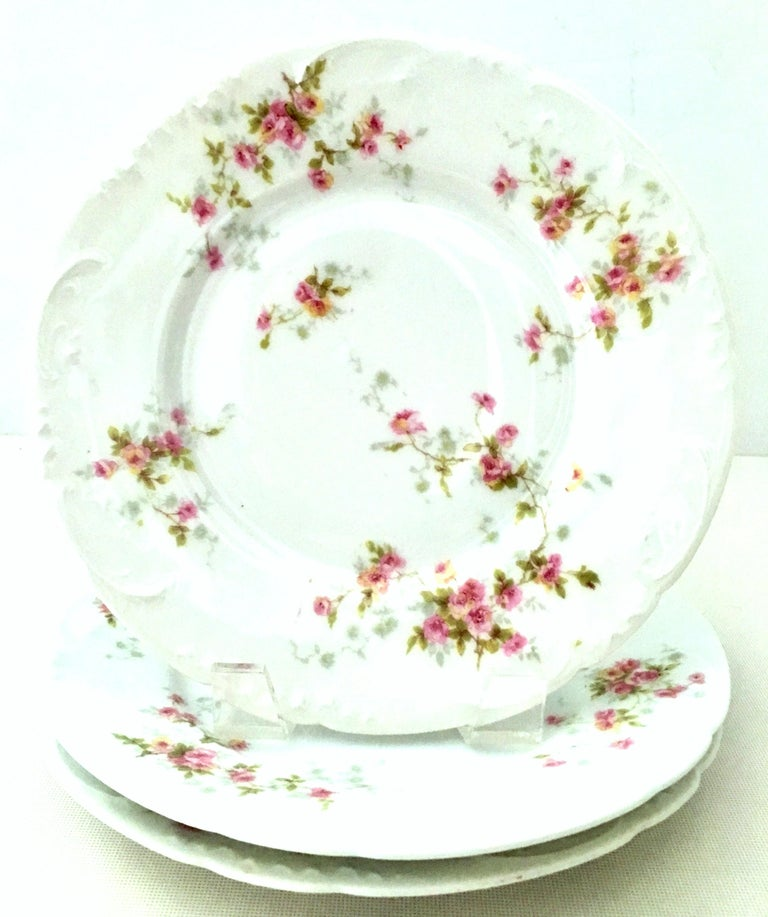 20th century French Limoges dinnerware by Theodore Haviland set of nine pieces. Set features a bright white ground with scalloped shape detail, hand painted in a bright pink and green flowing rose pattern. This nine piece set includes, three dinner