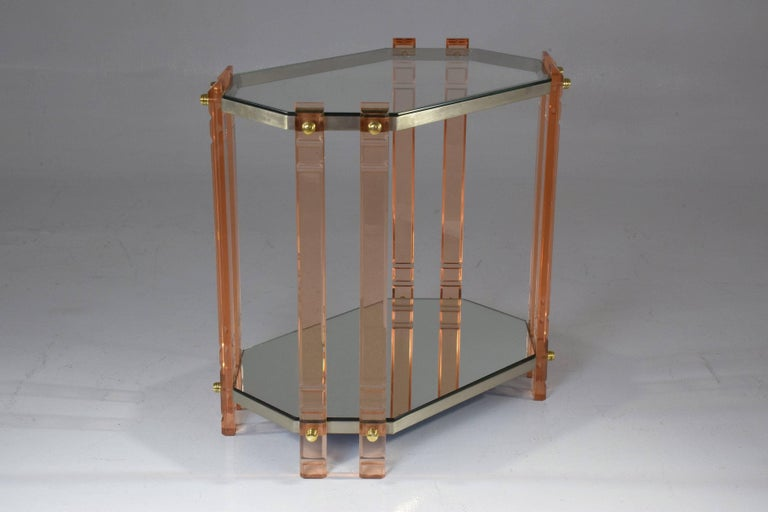 A 20 century French vintage storage piece, accent table, étagère or bar cart composed of a light pink plexiglass structure with polished brass screws, stainless steel shelves with mirrored glass table tops. This piece will highlight any living area