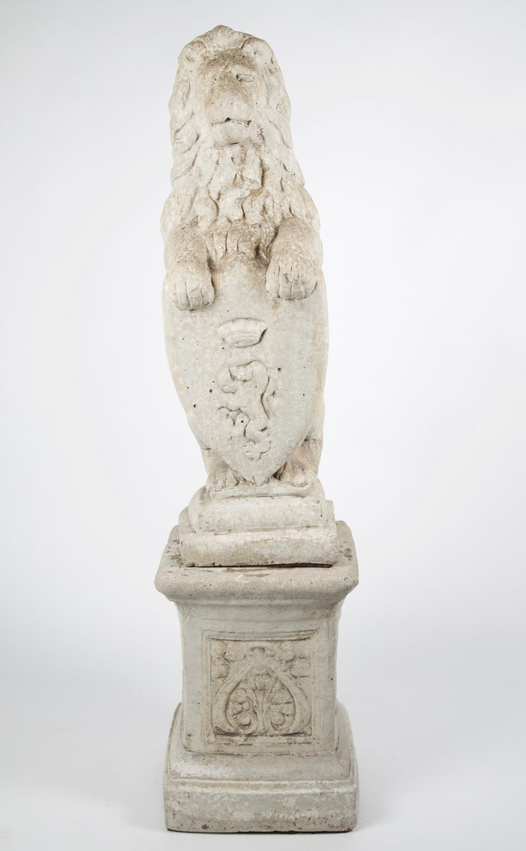 20th century French stone lion holding a shield on a pedestal. A 20th century lion carved from stone holding a crest carved with a lion with wearing a crown. It is a representation of power having exquisite detail while sitting atop a plinth base