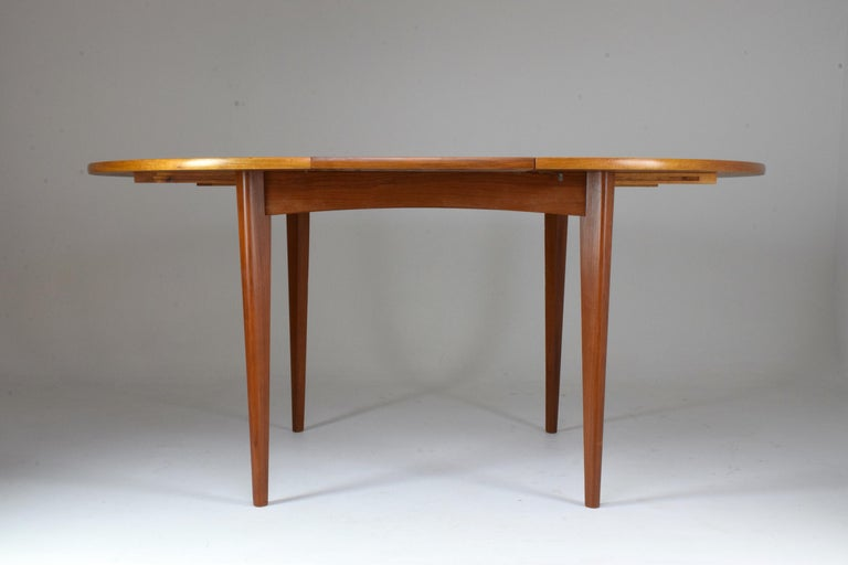 A Mid-Century Modern adjustable circular re-finished dining table of simple yet sophisticated Scandinavian style in solid teak sitting on tapered legs and fully functioning extensions. Fits 4 to 6 people. Useful for dining areas.  All our pieces are