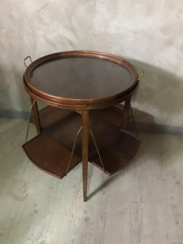 Very nice and original 20th century French walnut and glass tea table from the 1920s.  Brass net all along the table. Glass table removable thanks to brass handles.  Four opening and closing shelves on the second part of the table.  Used for