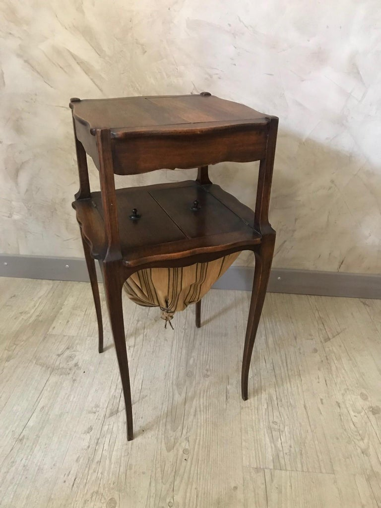 Very nice 20th century French walnut sewing table from the 1920s. Opening on the top to show multiple storage compartment. Also opening on the bottom to put all the sewing things in the fabric compartment. Nice quality and condition.