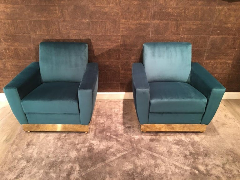 Pair of Italian  armchairs with a rectangular shape. They are very comfortable and enveloping. They are covered in turquoise velvet. The structure rests on a solid wooden base covered in polished brass. To facilitate movement, there are four little