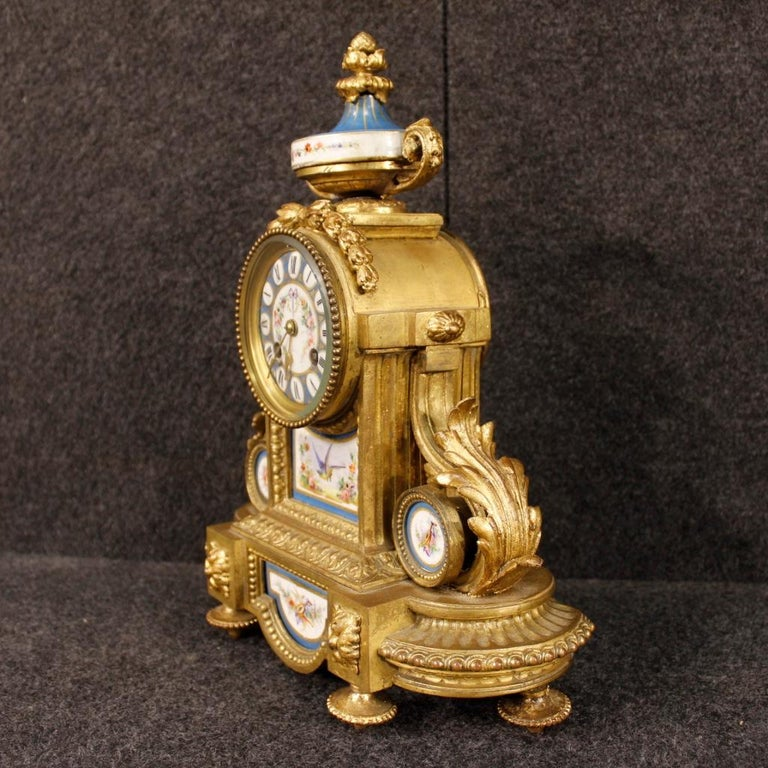 French clock from the mid-20th century. Object in gilded and chiselled bronze and brass, adorned with hand-painted ceramic elements with floral decorations of great pleasure. Rear door with glass to be replaced (see photo), mechanism not working, to