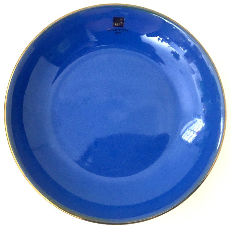 20th century Givenchy Paris porcelain cobalt enamel & 22k gold bowl. Features a vivid cobalt base with a 22K gold rim. Can be used as a serving and or decorative bowl. Givenchy Paris logo appears on front of piece. Signed on the underside,