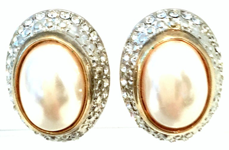 20th Century Givenchy Style Pair Of Two Tone Austrian Crystal & Faux Pearl Earrings. These silver and gold plate base metal clip style earring feature a large oval faux pearl bezel set stone surrounded by brilliant colorless cut and faceted Austrian
